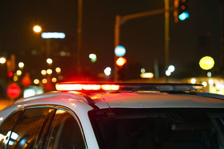 Closeup of red lights on top of a police vehicle at night. Selective focus, blur.
