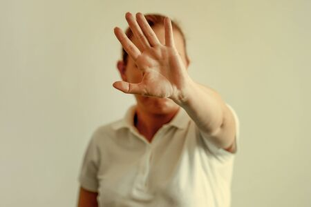 Woman holding her hand stretched out toward the camera, covering her face, avoiding to be seen or stopping a problems.