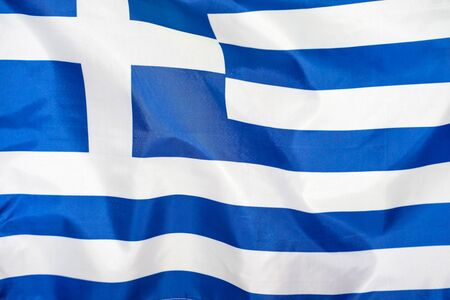 Fabric texture flag of Greece. Flag of Greece waving in the wind. Greece flag is depicted on a sports cloth fabric with many folds. Sport team banner.