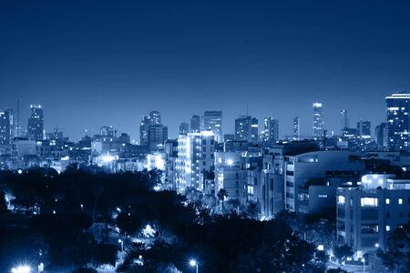 Night view of the city life. Light of the buildings shining with cool blue tones. View of night scene of Tel Aviv, Israel. Blue tone city scape. Selective focus. Imagens