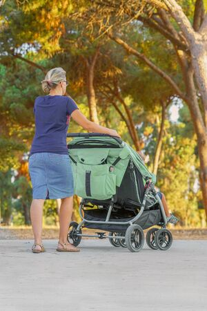 Young mom with baby carriage. Woman with a baby carriage for two children walks in the park on a summer morning. Walking. Back view.