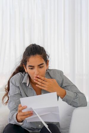 Portrait of office worker woman vomits letter, document. Woman reads negative news in a letter. Shocked beauty girl business manager received layoff message letter from company feeling surprised.