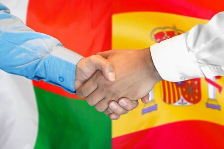 Business handshake on the background of two flags. Men handshake on the background of the Madagascar and Spain flag. Support concept. Stock Photo