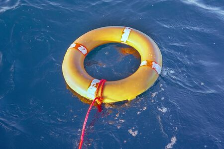 Yellow lifebuoy with a rope in blue sea on water. Life ring floating on top of water. Life ring with a rope in ocean.