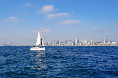 Sailing yacht on the background of the coastline of the city of Tel Aviv. Concept of water tourism. Sailing a yacht.