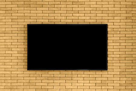 Blank black tv on the brown brick wall with copy space. TV display on old brick wall background. Mockup.