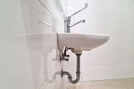 Public washbasin in the airport or restaurant, cafe. White washbasin interior sink with modern design. Close-up of bathroom. 免版税图像