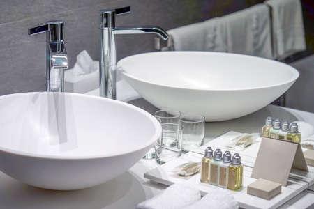 Modern white bathroom sink with faucet. Bathroom interior sink with modern design in luxury hotel.