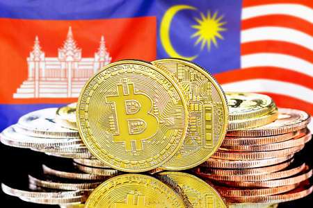 Concept for investors in cryptocurrency and Blockchain technology in the Cambodia and Malaysia. Bitcoins on the background of the flag Cambodia and Malaysia.