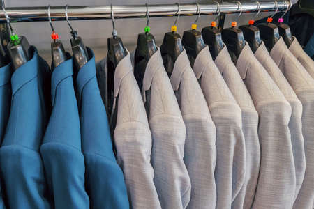 Men row of blue and white suits on hanger. Men clothes hanging on wooden hangers in a store. Men's suits on hanger. Row of men's suit jackets