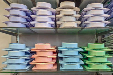 Folded mens shirts in a store. Shelves with a lot of colorful shirts neatly folded in the store clothes and business suits. Banque d'images