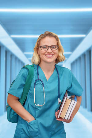 Fmale nurse or intern surgeon with eyeglasses in blue uniform with books and bag on the background of a blurred corridor of the clinic. Health care banner. Education concept. Banque d'images