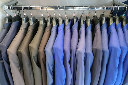 Men row of suits on hanger. Men clothes hanging on wooden hangers in a store. Men's suits on hanger. Row of men's suit jackets