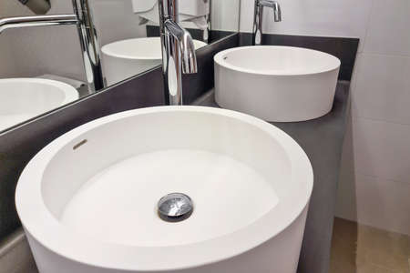 Modern white bathroom sink with faucet. Bathroom interior sink with modern design in luxury hotel.