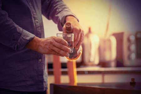 Hands of elderly caucasian man with bottle of whiskey on the kitchen. The concept of drunkenness and alcoholism. Alcoholic father. Toning Banque d'images