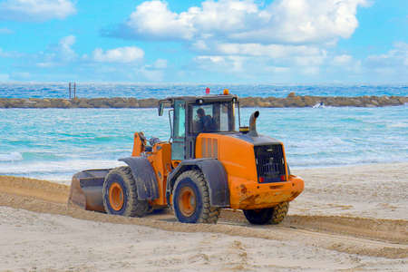 Bulldozer and a panoramic view of the sea. Yellow bulldozer in front of the sea. Banque d'images