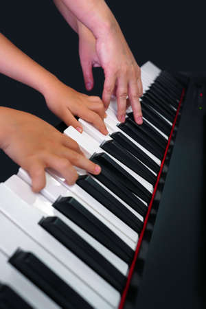 Children's hands and teacher's hands on the piano keys.  children's hands plays the piano, learning a lesson, black and white keys. Training on a synthesizer. Selective focus