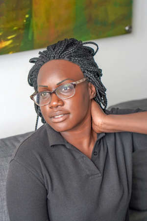 African american woman in spectacles sitting on sofa and has neck pain. Close up of african woman in neck and shoulder pain and injury. Healthcare and medical concept.