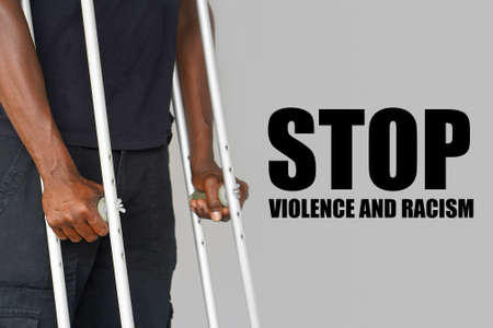 African man on crutches on a gray background. The concept of violence and racism in USA and the world