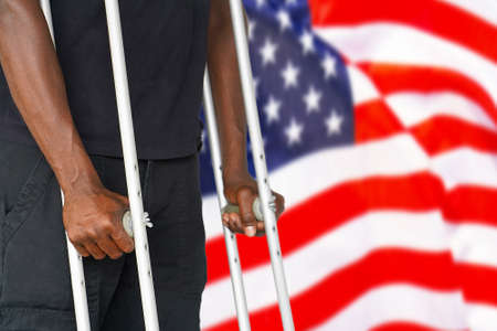 African man on crutches on the background of the USA flag. Disabled veterans of the US Army. The concept of stop violence and racism in USA 免版税图像