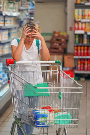 Upset woman in a supermarket with an empty shopping trolley. Crises, rising prices for goods and products. Woman shopping at the supermarket. 免版税图像