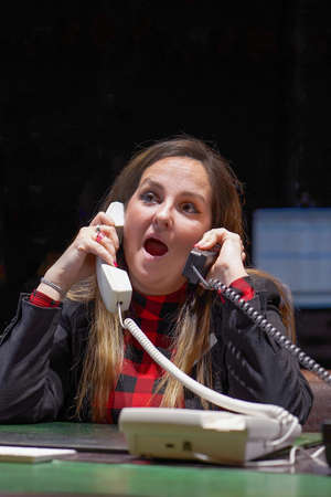Woman with phone tubes sitting at the table. Female hotel manager is under stress answers. A lot of phone calls. Funny facial expression, emotions, feelings, problems reaction, stress.