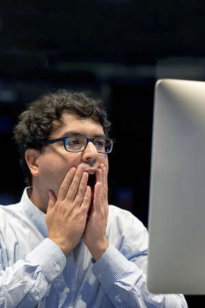 Indian man in stress in front of a computer. Poor economy concept. Face expression, emotion. Body And Health Care Concept. 免版税图像