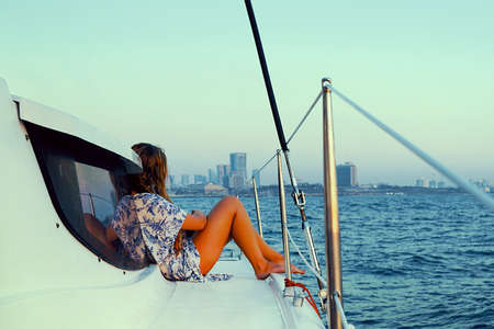 Young woman in a dress sits on the deck of a sailing yacht. Back view of woman in blue dress enjoying azure water on the deck of a sailing yacht. Concept of sailing regatta, luxury vacation at sea. 免版税图像