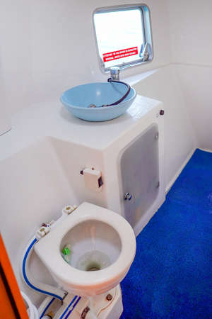 Yacht toilet of yacht interior comfortable for holiday. A view of a toilet in yacht. White Toilet restroom inside Yacht with Window, wash wc on ocean boat