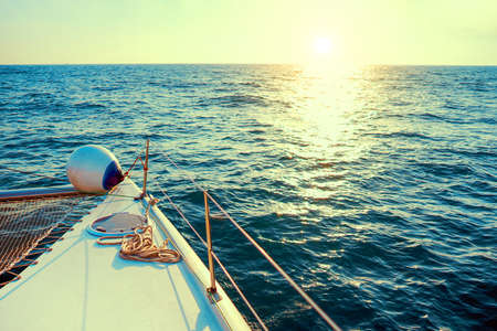 The yacht at sunset. Sailing boat in the sea during sunset. Yachting as a luxury sport and great vacation.