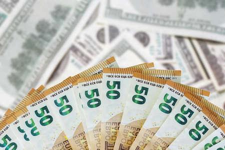 Fan euro banknotes. Fan 50 euro banknotes on blur american dollars background. 免版税图像
