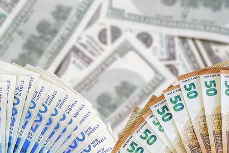 Fan euro banknotes and new Israeli shekel. Fan 50 euro banknotes and 200 Israeli money banknotes on blur american dollars background. 免版税图像