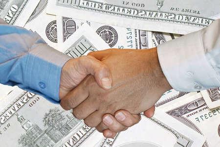 Handshake of two hands men closeup on background hundred dollar banknotes. Handshake over 100 dollar bills. Image of handshake a trusted Business partnership with US dollar bank note background.