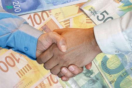 Handshake of two hands men closeup on background of Israeli money banknotes. Handshake over new Israeli shekel. Image of handshake a trusted Business partnership with Israeli money background.