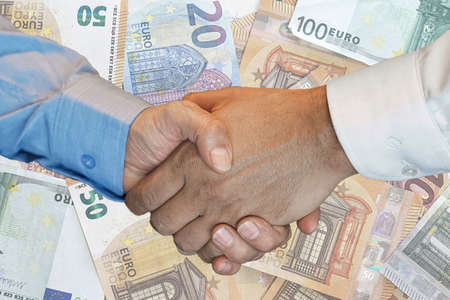 Handshake of two hands men closeup on background euro banknotes. Handshake over euro money. Image of handshake a trusted Business partnership with euro bank note background.