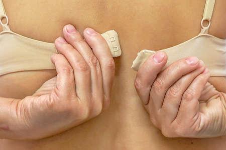 Closeup of woman hands unfastening bra. Lower lingerie. Female hands unfasten the bra. Back view 免版税图像