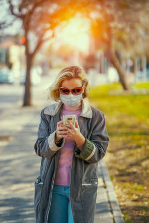 Woman wearing medical mask in street in city and writes SMS via smartphone. Woman walking on the street wearing protective mask as protection against infectious diseases.