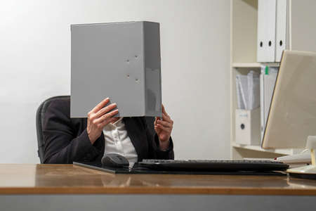 Woman covers her face with a folder of documents. A lot of paper work in office. Stress on workplace in office. 免版税图像 - 153118811