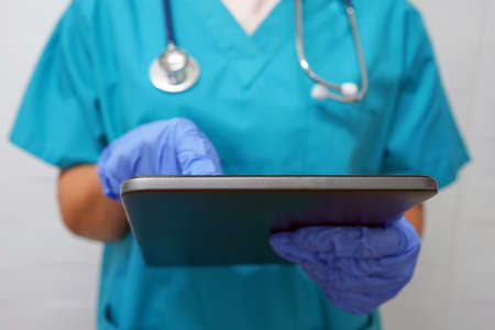 Surgeon or doctor woman in gloves using digital tablet. Surgeon in gloves writes texting on digital tablet.