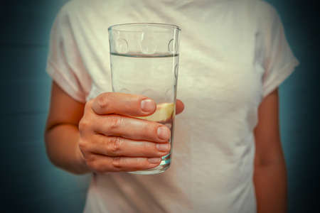 Womans hand holding a glass of water. Close-up of a glass. Closeup of female's hand holding glass of water. Refreshment and detox concept. Nutrition concept 免版税图像 - 153118817