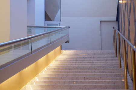 Wide staircase to the hotel lobby. Stairway in office building. Closeup and details of railing and stairs of a modern building, theater or concert hall.