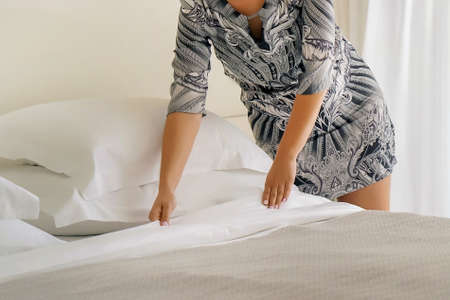 Hands of woman maid making bed in hotel room. Housekeeper Making Bed 免版税图像 - 153118821