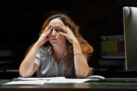 Woman office worker is distressed with a lot of paperwork. A lot of paper work in office. Night time