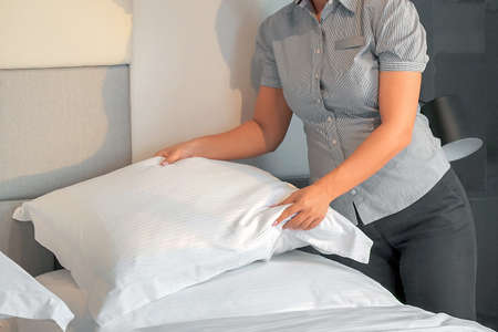 Hands of woman maid making bed in hotel room. Housekeeper Making Bed 免版税图像 - 153118824