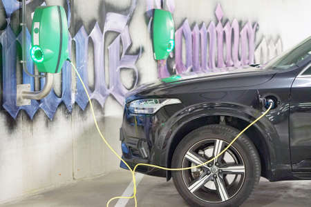 Electric car charging on parking lot with electric car charging station. Close up of power supply plugged into an electric car being charged. 31 August 2018. Parking area. Amsterdam. Netherlands 新闻类图片