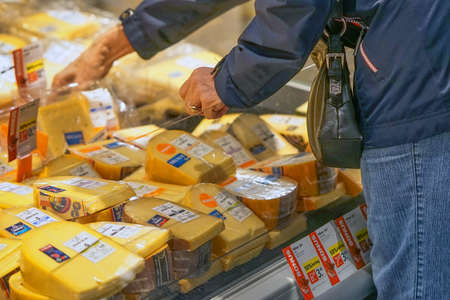 Closeup elderly womans hands picking cheese inside superstore. Old woman choose cheese in supermarket. Female pensioner choosing cheese in grocery store. 7 September 2018. Rotterdam. Netherlands 新闻类图片