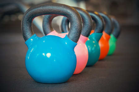 Colorful kettlebells in a row in a gym. 免版税图像