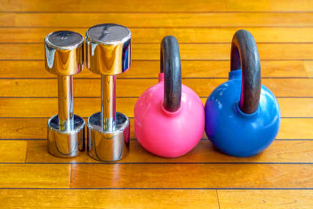 Kettlebell and chrome dumbbell on the wooden floor in the gym
