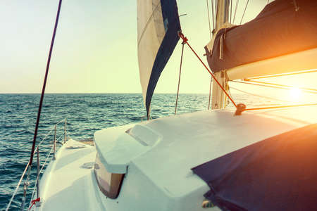 Sailing catamaran at sunset in the sunin the sea high speed in a strong wind during the regatta with sea on the background. Yachting as a luxury sport and great vacation.