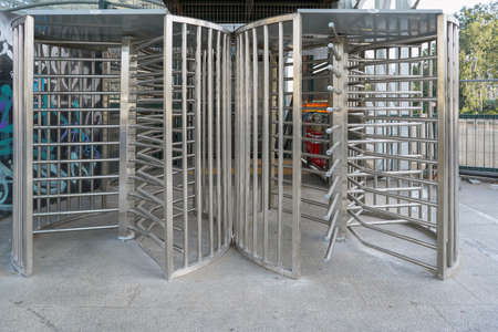 Protected entrance gate - secured turnstiles outdoors. Steel revolving turnstiles at the entrance of production or metro station. Closeup of steel revolving security turnstile on the street 免版税图像